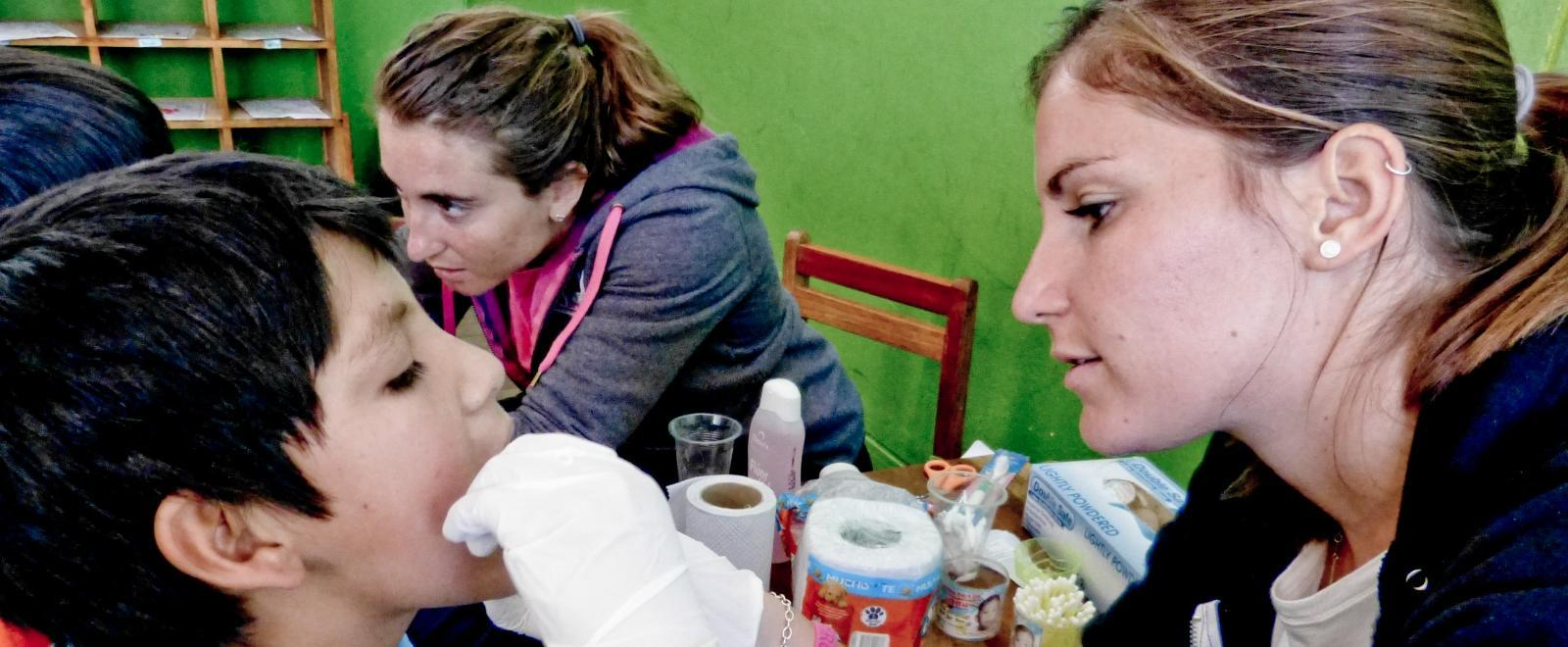 A projects abroad intern is seen giving a check up to a local boy whilst on her nursing work experience in Peru.